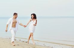 Couple running  together  at seaside Royalty Free Stock Images