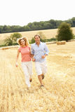 Couple Running Together Through Summer Harvested F. Ield Having Fun Royalty Free Stock Photo