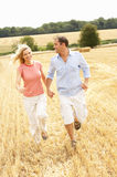 Couple Running Together Through Summer Harvested F. Ield Having Fun Stock Photos