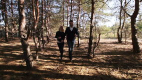 Couple running among trees stock video footage