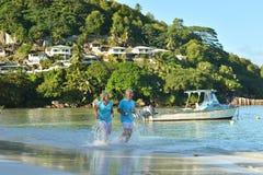 Couple running on  tropical beach. Happy elderly couple running on  tropical beach Royalty Free Stock Photo
