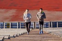 Couple running upstairs on stadium Stock Photos