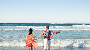 Couple Running Through Waves On Beach Holiday Royalty Free Stock Image