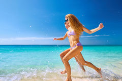 Couple Running Through Waves On Beach Holiday. Happy Couple Running Through Waves On Beach Holiday Royalty Free Stock Photography