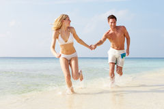 Couple Running Through Waves On Beach Holiday Royalty Free Stock Photo