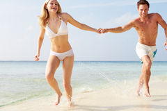Couple Running Through Waves On Beach Holiday. Towards Camera Royalty Free Stock Images