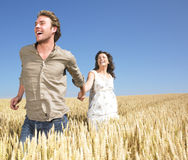 Couple running in wheat field Stock Photo
