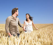Couple running in wheat field Royalty Free Stock Photo