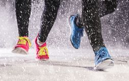 Couple running in winter. Athlete woman and man are running during winter training outside in cold snow weather Stock Image