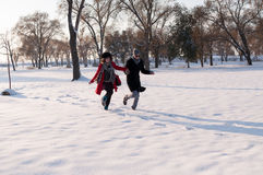 Couple running in winter forest Royalty Free Stock Photography