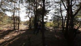 Couple running among wood stock video footage