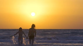 Couple runs and enjoys on the beach at sunset. Happy Man with woman is holding hands and running on the shore of the sea. In water. Two people in love, have fun stock footage