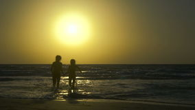 Couple runs and enjoys on the beach at sunset. Happy Man with woman is holding hands and running on the shore of the sea. In water. Two people in love, have fun stock video footage