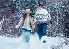 Couple runs and throws snow Stock Photos