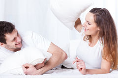 Couple's bed pillow fight. A young happy couple having a pillow fight in bed stock image