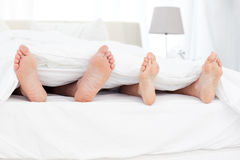 Couple's feet in the bed Stock Photo