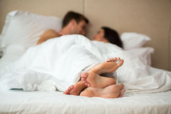 Couple`s feet in bed. Man with women under blanket. Rest in home comfort Royalty Free Stock Images