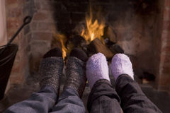 Couple's feet warming at a fireplace Stock Photography