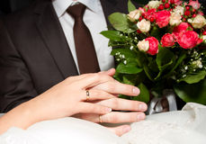 Couple's hands. On the bouquet Stock Image