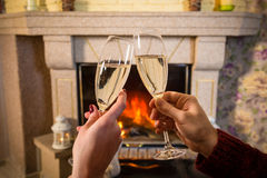 Couple`s hands with glass of champagne near fireplace Royalty Free Stock Photo