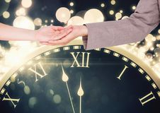Couple`s hands holding over magical time clock with sparkles Royalty Free Stock Images