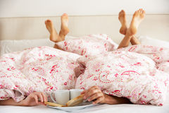 Couple's Hands Reaching From Under Duvet. For Breakfast Stock Photo