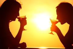 Couple's silhouettes on sunset drink from glasses Royalty Free Stock Images
