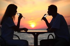 Couple's silhouettes on sunset drink from glasses Royalty Free Stock Photos