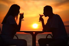 Couple's silhouettes on sunset drink from glasses Royalty Free Stock Photo