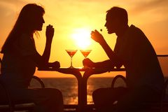 Couple's silhouettes on sunset sit at table Stock Images