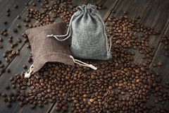 A couple of sacks of roasted arabica coffee beans. On a dark wooden background Royalty Free Stock Images