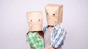 A couple with sad faces with paper bags on their heads. On a gray background stock footage