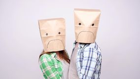 A couple with sad faces with paper bags on their heads. On a gray background stock video