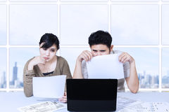 Couple sad looking at laptop in office Stock Images
