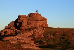 Couple on Saddle Tor at Sunset. The sun sets whilst a couple stand on top of Saddle Tor - a natural granite rock formation - on Dartmoor, Devon, in England Royalty Free Stock Image