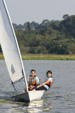 Couple Sailing Across Lake - Vertical. Man and woman sitting on sailboat leaning out over water and smiling at camera. Sailing across lake. Vertically framed Stock Photos