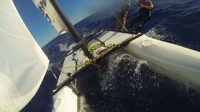 Couple sailing rapidly on windsurf catamaran, controlling it by standing on hull