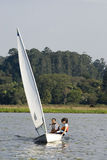 Couple Sailing - Vertical. Man and woman leaning out over water while sailing. Front view. Moving toward camera. Vertially framed photo Stock Images