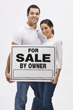 Couple With For Sale By Owner Sign. An attractive, young couple holding a 'For Sale By Owner' sign. They are smiling and are looking directly at the camera royalty free stock photography