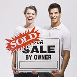 Couple with For Sale by Owner Sign Royalty Free Stock Photos
