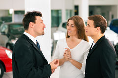 Couple with salesman at car dealer stock photography
