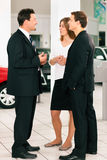 Couple with salesman at car dealer. Sales situation in a car dealership, the dealer is talking to a young couple, there are cars standing in the background Royalty Free Stock Photography