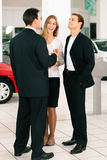 Couple with salesman at car dealer Stock Photos