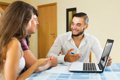 Couple and salesman talking. Young couple and smiling salesman talking cheerfully about purchase at home stock photo
