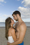 Couple in the Sand. Young healthy couple kissing in the beach Royalty Free Stock Photography