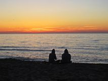 Couple at Sand Beach during Romantic Sunset with Clouds royalty free stock images