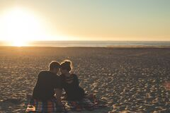 Couple on sandy beach at sunset Stock Photos