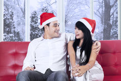 Couple in santa hat sitting on red couch Stock Photo