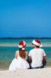 Couple in Santa hats at beach Stock Image