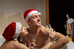 Couple in santa hats is enjoying a bath Stock Image